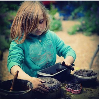 child in a green hoodie playing with mud and a variety of kitchen utensils