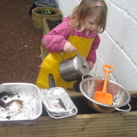 child pouring water from a kettle into a bowl