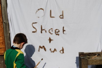 white sheet hung on a fence with words painted in mud: old sheet & mud, with small boy in green overalls holding paintbrush to one side