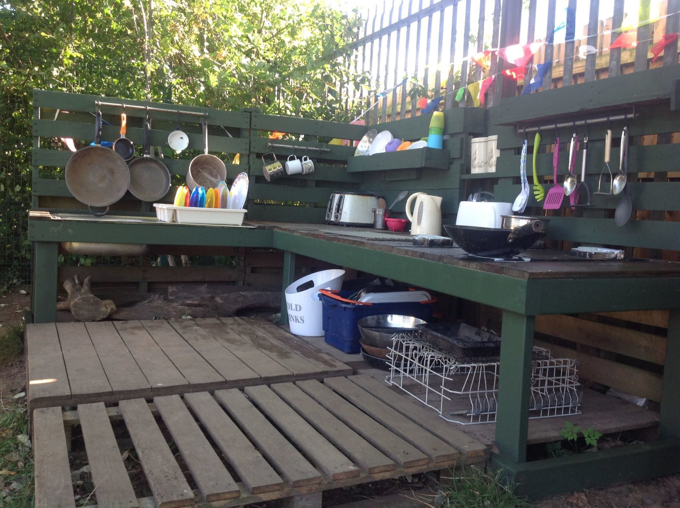 2 wooden palletts on the ground, 2 mud kitchen benches and lots of kitchen utensils