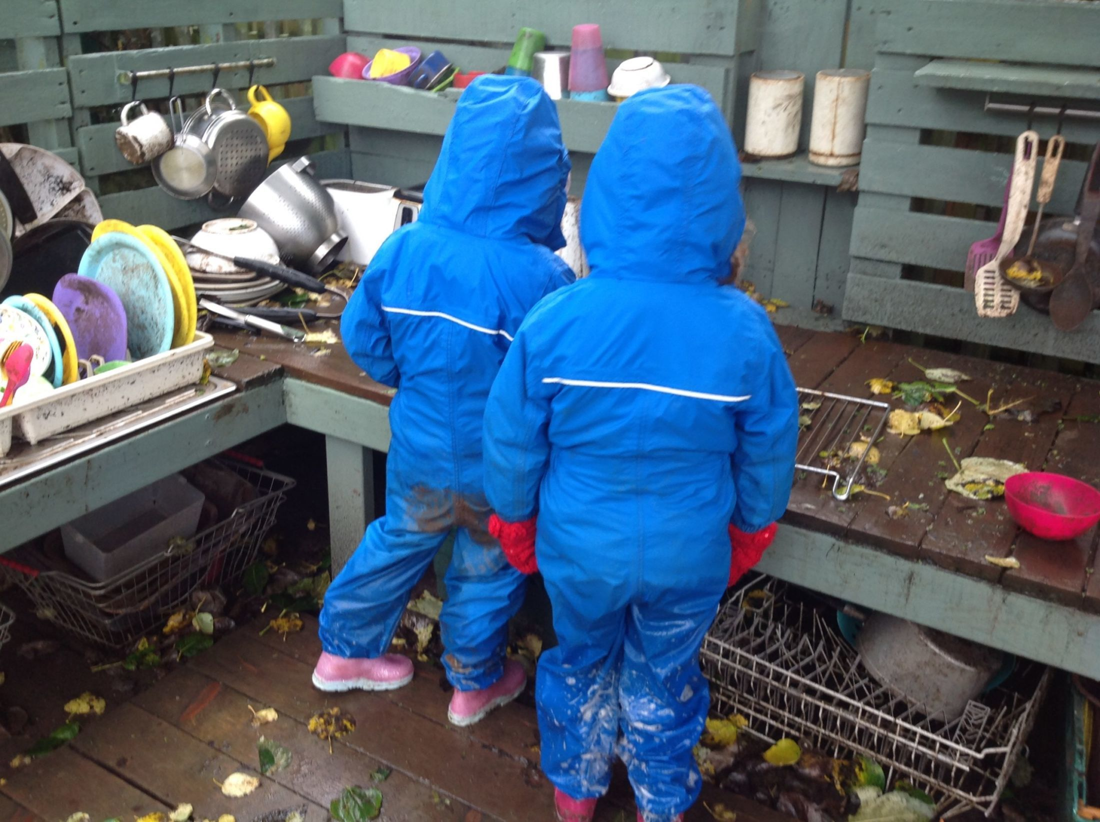 2 small children in all in e blue waterproof suits playing in a mud kitchen