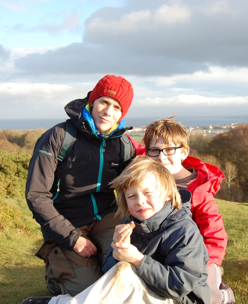 Liz and her two sons, all wrapped up in waterproofs, kneeling on top of a hill with the city in the distance