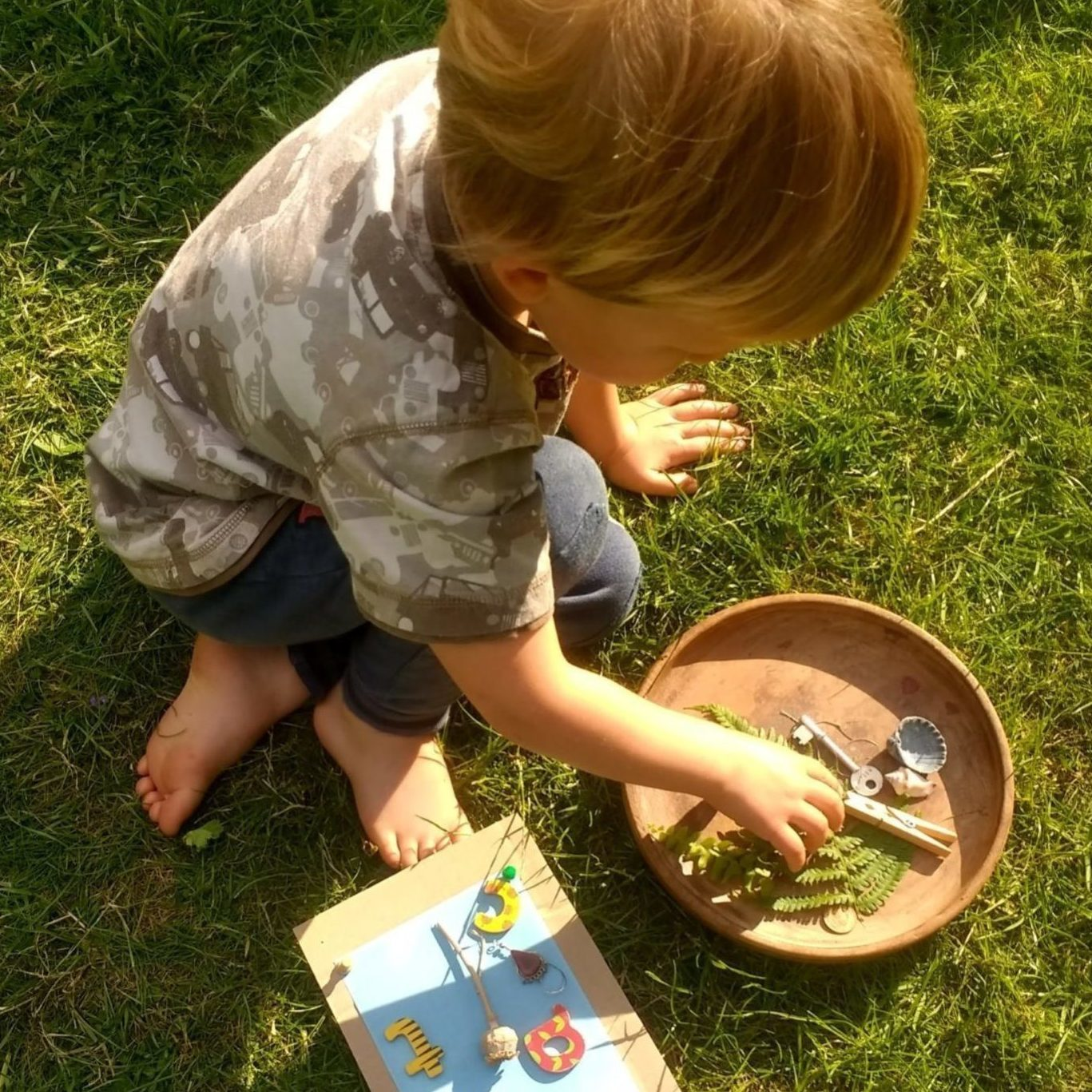 small child kneeling on grass with their hand in a bowl of ferns and shells and other natural objects