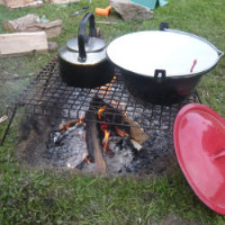 campfire and grill with kettle and large jam pan on top