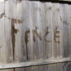 the word fence written on a fence in water