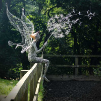 wire sculpture of fairy blowing a dandelion clock sitting on fence