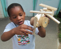 little boy holding up a handmade wooden helicopter