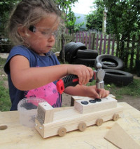 girl wearing safety goggles hammering a nail into a wooden train that she is making