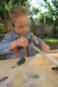 little girl in denim jacket and plastic goggles, hammering a nail into a piece of wood, on a workbench with pots of nails and screws and a screwdriver