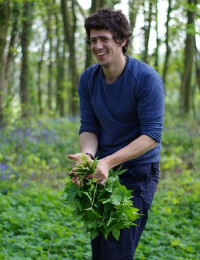 man in a bluebell wood holding a big bunch of elder leaves
