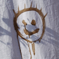 smiley face drawn in mud