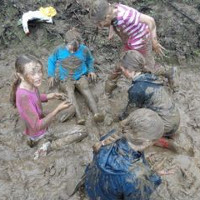 a gang of girls sitting in a mud puddle