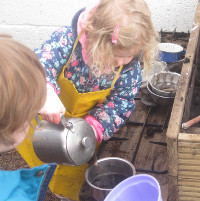 child pouring water into a teapot