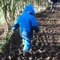 child in waterproofs stomping through mud