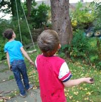 boys throwing mud at a tree