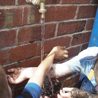 washing hands with an outdoor tap