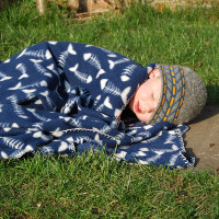 small child lying on the grass under a blanket sleeping