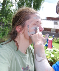 woman having her face painted with mud