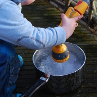 child running a hose into a saucepan