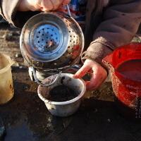 boy pouring mud through a sieve into a pot