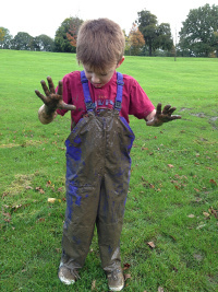 boy in very muddy dungarees
