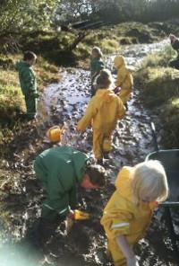 children in waterproofs paddling in a muddy stream