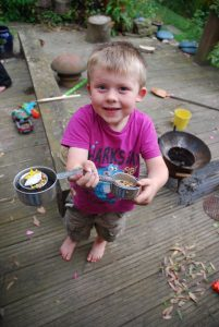 small boy in purple tshirt and shorts, holding up measuring jugs full of mud and petals, standing on a deck with mud kitchen items